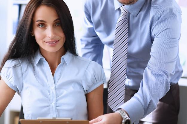 Dos empleados en el lugar de trabajo de la oficina examinando algunos documentos financieros