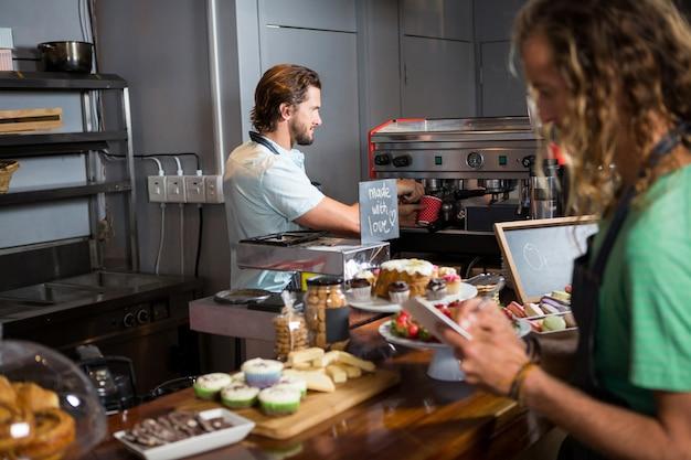 Dos empleados masculinos que trabajan en el mostrador