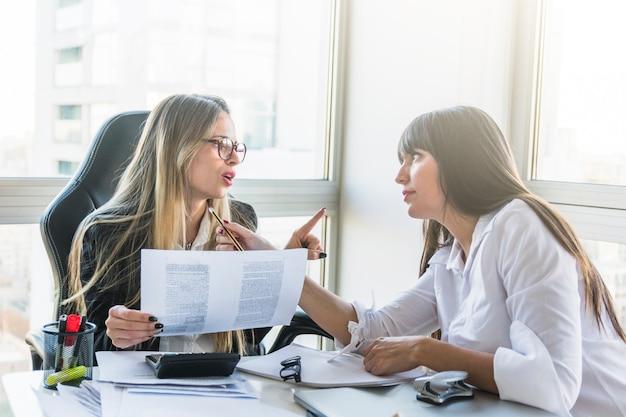 Dos empresaria discutiendo entre sí en la oficina