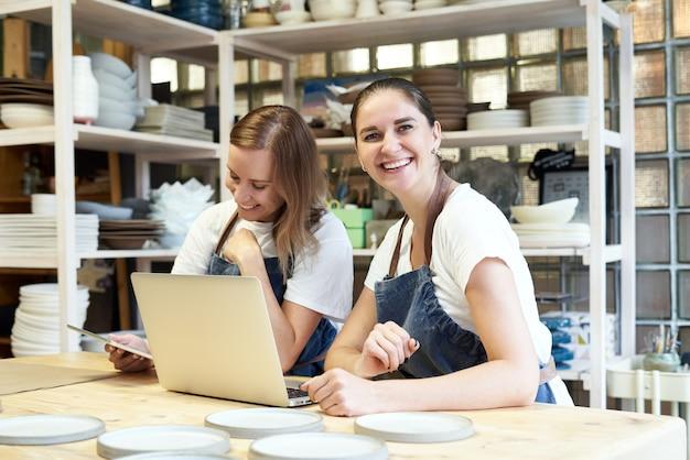 Dos empresaria sonriente con portátil en el taller artesanal.