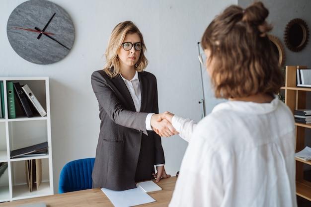 Dos empresarias dándose la mano en la oficina