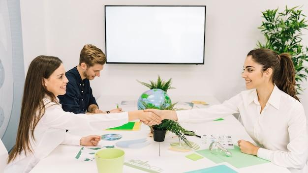 Dos empresarias felices agitando las manos sobre el escritorio