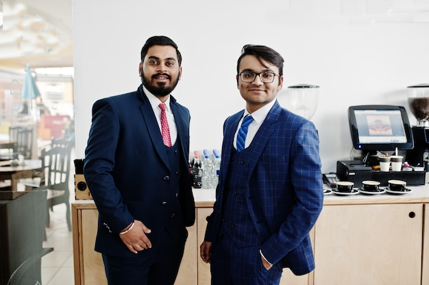 Dos empresario indio en trajes de pie en la cafetería.