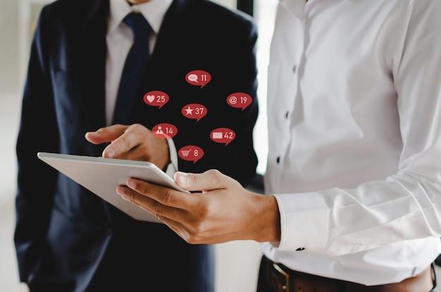 Dos empresario trabajando con tableta móvil para red social