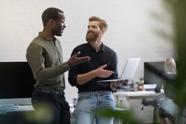 Dos empresarios alegres discutiendo algo en la computadora portátil y sonriendo