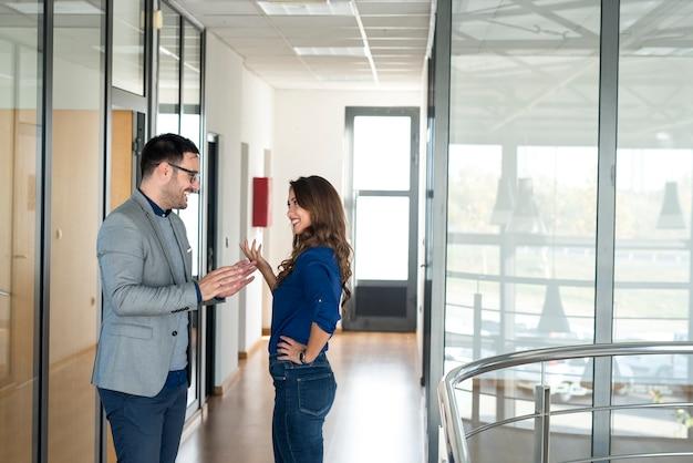 Dos empresarios conversando en el pasillo corporativo de la oficina.
