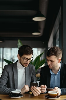 Dos empresarios conversando con un teléfono inteligente