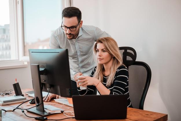 Dos empresarios coworking con una computadora en un escritorio en la oficina.