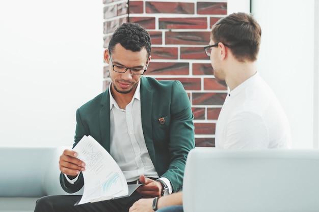 Dos empresarios discutiendo documentos financieros en la oficina.