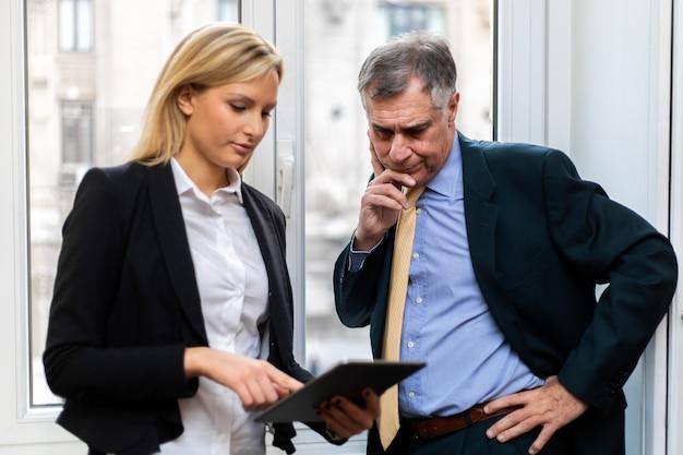 Dos empresarios discutiendo mientras mira una tableta