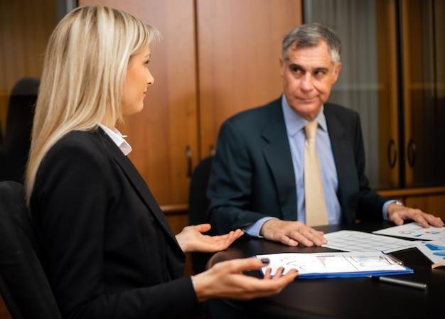 Dos empresarios discutiendo sentado en el escritorio en su oficina
