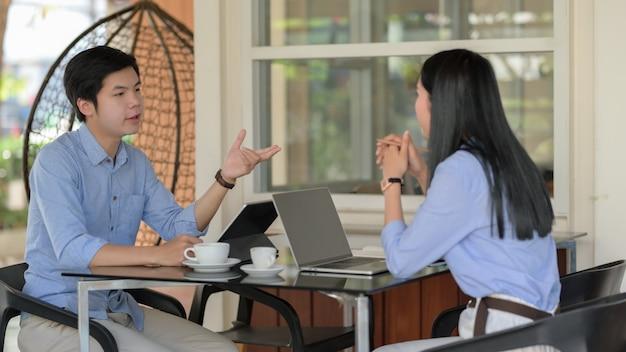 Dos empresarios discutiendo sobre su trabajo con laptop