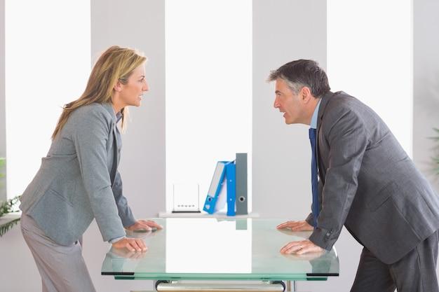 Dos empresarios enojados discutiendo a cada lado del escritorio