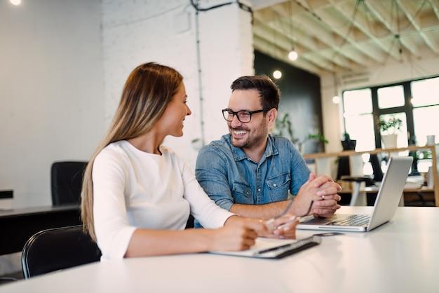 Dos empresarios hablando en la oficina moderna.