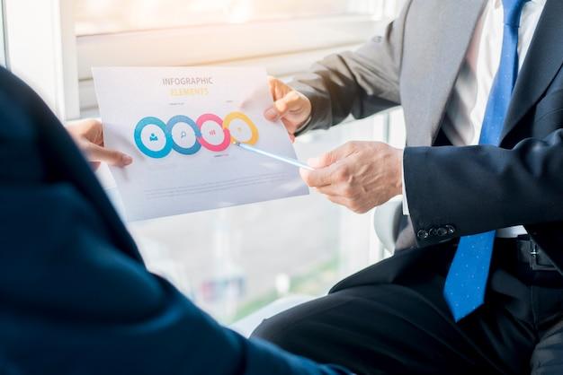 Dos empresarios con hoja de elementos de infografía