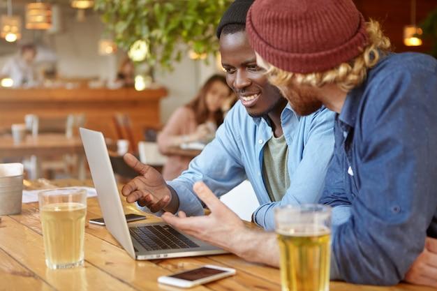 Dos empresarios masculinos con estilo de diferentes razas beben cerveza mientras tienen una reunión de negocios en el bar, discuten un proyecto de inicio común, hablan sobre la estrategia y los planes futuros usando una computadora portátil