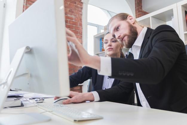 Dos empresarios mirando el monitor sentado en la oficina