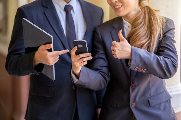 Dos empresarios de pie en la oficina mirando el teléfono móvil inteligente.