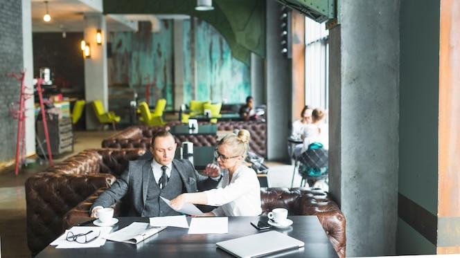 Dos empresarios sentados juntos comprobando el documento en café