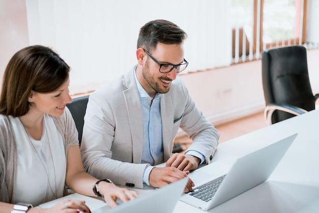 Dos empresarios sentados juntos trabajando en un escritorio de oficina con laptop