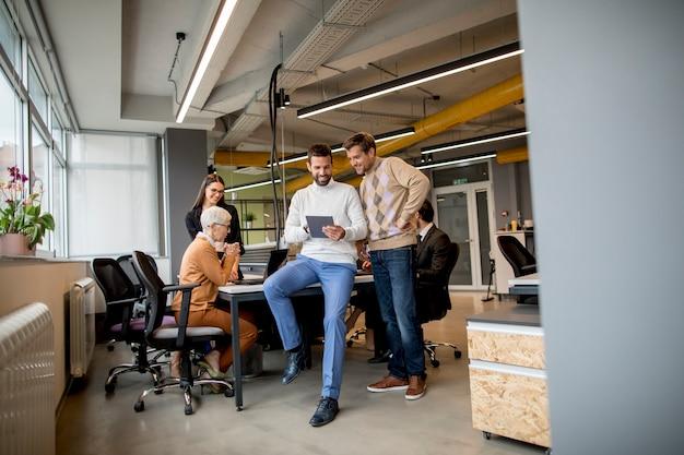Dos empresarios con una tableta digital en la oficina moderna