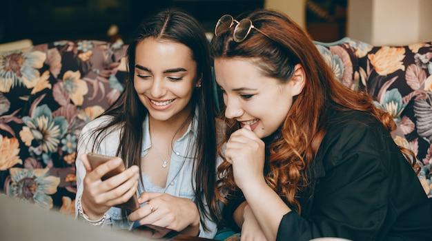 Dos encantadoras hembras jóvenes mirando la pantalla de un teléfono inteligente riendo mientras están sentados en una cafetería.