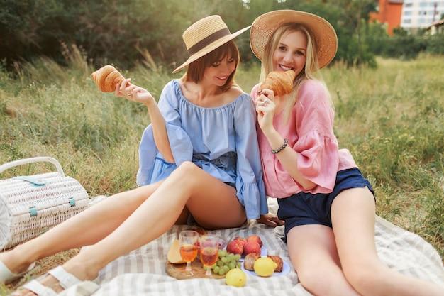 Dos encantadoras mujeres juguetonas posando sobre el césped en el parque de verano, disfrutando de deliciosa comida, croissants y vino.