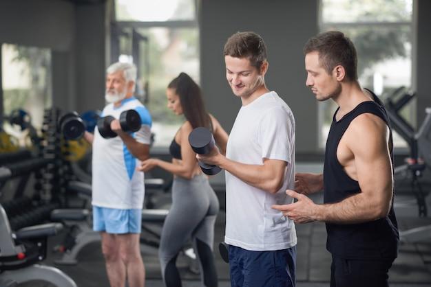 Dos entrenadores que trabajan con clientes en el gimnasio.