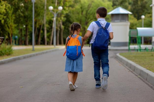 Dos escolares, una niña y un niño con mochilas corren camino al parque verde.