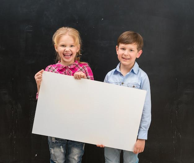 Dos escolares sonrientes con una hoja de papel en blanco