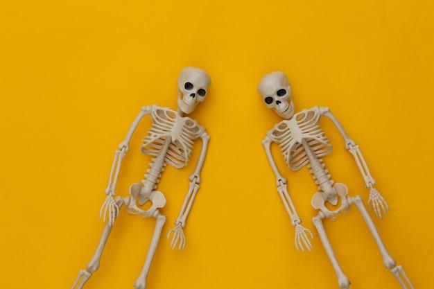 Dos esqueletos falsos en amarillo. decoración de halloween, tema de miedo