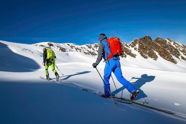 Dos esquiadores alpinistas durante un viaje de esquí de montaña