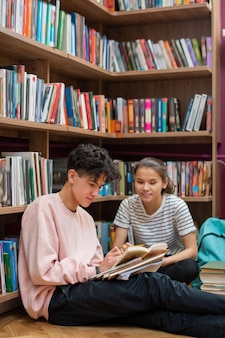 Dos estudiantes adolescentes inteligentes sentados en el suelo de la biblioteca de la universidad por estantería y discutiendo el pasaje de la historia