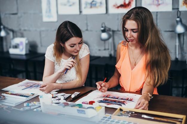 Dos estudiantes adultas que trabajan en sus pinturas estudiando en la escuela de arte