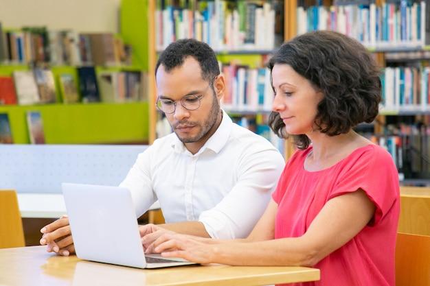 Dos estudiantes adultos colaborando en proyecto en biblioteca