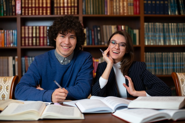 Dos estudiantes alegres realizan juntos el proyecto sentados en la biblioteca.