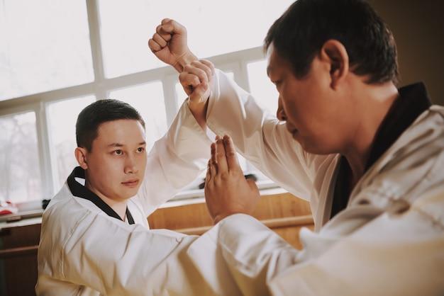 Dos estudiantes de artes marciales en blanco luchan juntos.