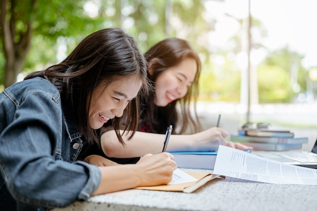 Dos estudiantes asiáticos están trabajando juntos para hacer una tesis para enviar profesores a universidades