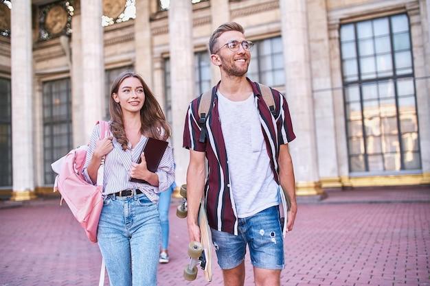 Dos estudiantes enfocados con mochilas sobre sus hombros salen de un edificio de mármol