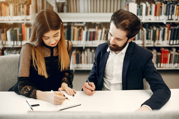 Dos estudiantes estudiando en la biblioteca.