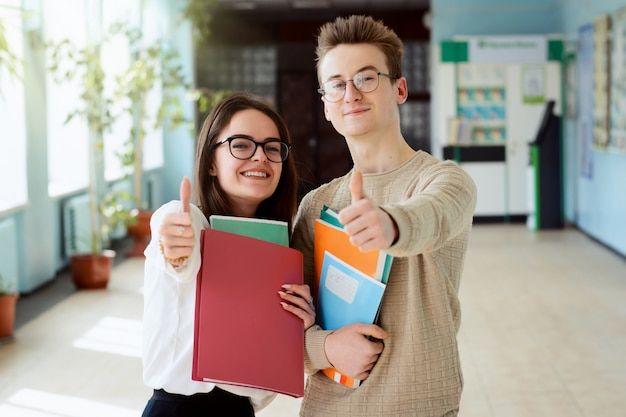 Dos estudiantes felices de buen humor mostrando los pulgares para arriba