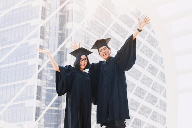 Dos estudiantes felices celebrando la graduación exitosa en el fondo del edificio del campus