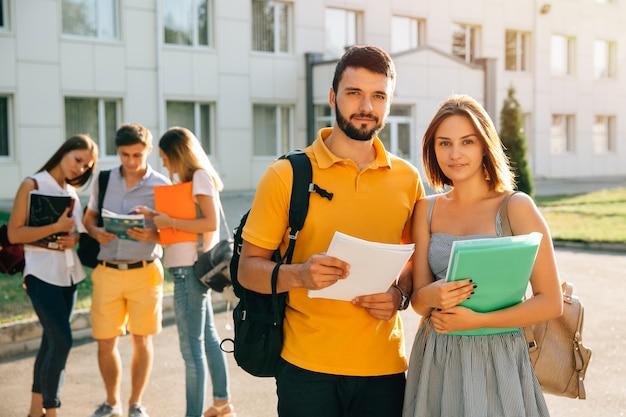 Dos estudiantes felices con mochilas y libros en sus manos sonriendo a la cámara