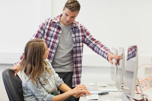 Dos estudiantes felices trabajando en computadora
