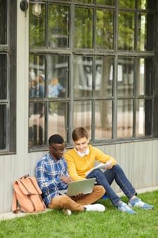 Dos estudiantes haciendo la tarea en el campus