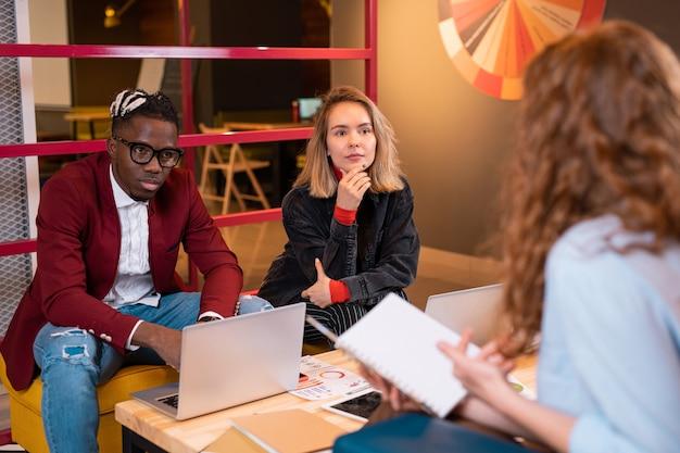 Dos estudiantes multiculturales serios escuchando a su compañero de grupo durante la discusión de la tarea en la cafetería de la universidad