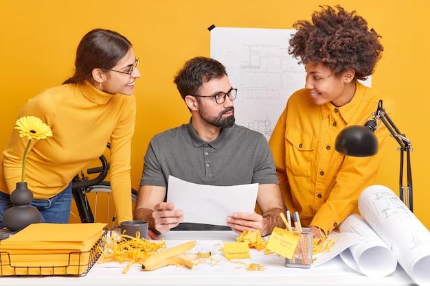 Dos estudiantes multinacionales tienen consultoría con un entrenador profesional, verifican el desembolso gráfico para el proyecto de arquitecto, brainstrom juntos, posan en el espacio de coworking, hacen planos y bocetos