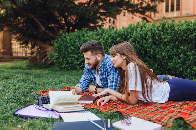 Dos estudiantes se sientan en el campus de césped y trabajan en una computadora portátil. hermosa chica y chico guapo en la universidad