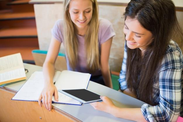Dos estudiantes sonrientes usando tableta en la universidad