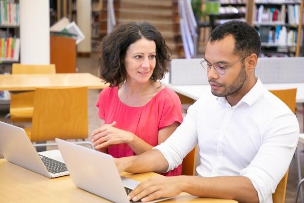 Dos estudiantes universitarios adultos conversando mientras trabajan
